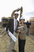 Two Engineers With Blueprint At Site - stock photo