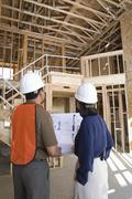 Architect With Foreman Examining Framework - stock photo