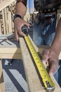Stock Photo of Man Measuring Wooden Beam