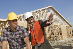 Architect On Call Gesturing Towards Site With Co-Worker - stock photo