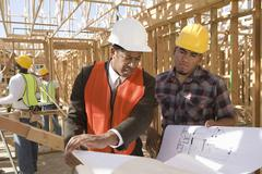 Architect And Foreman Having Discussion Over Blueprint Stock Photos