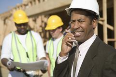 An Architect On Call With Workers In Discussion Stock Photos