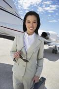 Stock Photo of Happy Businesswoman Standing On Airfield