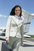 Stock Photo of Happy Businesswoman Walking On Airfield