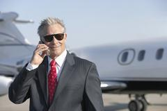 Businessman Using Cell Phone With Private Jet In Background - stock photo