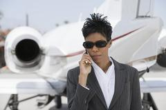Stock Photo of Confident Businesswoman Using Cellphone At Airfield