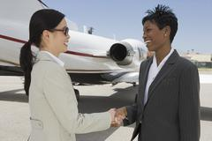Business Colleagues Shaking Hands At Airfield Stock Photos