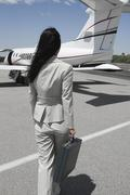 Businesswoman Walking Towards Private Airplane - stock photo