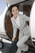 Businesswoman Getting Down From Airplane Stock Photos