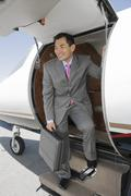 Businessman Standing On Ladder Of Private Airplane - stock photo