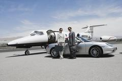 Business Couple Standing In Front Of Convertible And Private Jet Stock Photos