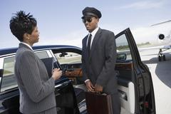 Stock Photo of Businesswoman Communicating With Driver On Airfield