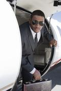 Businessman Getting Down From Airplane - stock photo