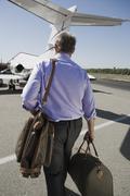 Stock Photo of Senior Businessman Walking Towards Airplane