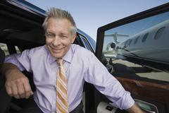 Senior Businessman Getting Down From Car - stock photo