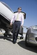 Stock Photo of Mature Business Walking At Airfield