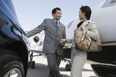 Business Person Holding Hands At Airfield - stock photo