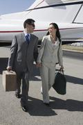 Business Couple Walking Together At Airfield Stock Photos