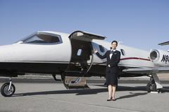Stock Photo of Stewardess Standing By Airplane At Airfield