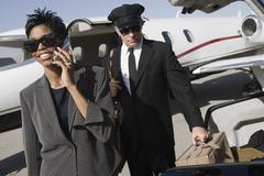 Stock Photo of Business Woman Using Cellphone At Airfield