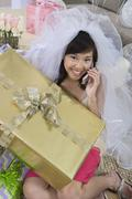 Stock Photo of Young Bride With Gift Communicating On Mobile Phone