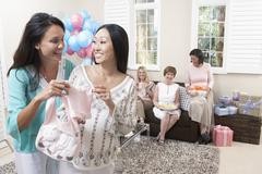Women Holding Baby Clothes At Baby Shower Stock Photos