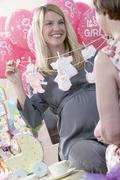 Pregnant Woman Holding Artificial Baby Clothes - stock photo