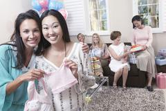 Woman Showing Off Gift At Baby Shower Stock Photos
