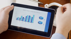 Business man looking at charts on tablet PC Stock Footage