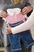 Woman Holding Baby Clothes On Pregnant Woman's Belly - stock photo