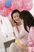 Woman Showing Baby Shower Clothes To Friend - stock photo