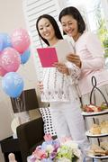 Stock Photo of Pregnant Woman And Friend Reading Greeting Card