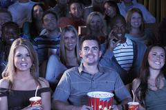 People With Soda And Popcorn Watching Movie In Theatre Stock Photos