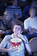 Man Eats Popcorn While watching Movie In Theatre - stock photo