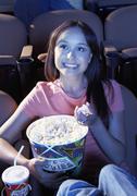 Nainen syö popcornia katsoessasi Movie Theater Kuvituskuvat
