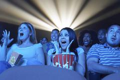 Young People Screaming While Watching Horror Movie In Theatre Stock Photos