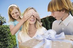 Kids Surprising Mother With A Gift - stock photo
