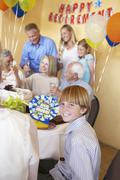 Boy Smiling With Family Having A Retirement Party Stock Photos