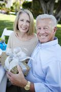 Stock Photo of Senior Couple Sitting With A Gift In Garden