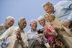 Senior Friends Watching Recorded Moments Together Stock Photos