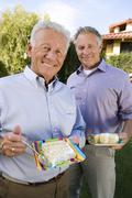 Senior Male Friends Eating Cake Stock Photos