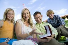 Happy Mature Woman Sitting With Family Stock Photos