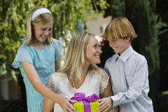 Mother Receiving Gift From Kids Stock Photos