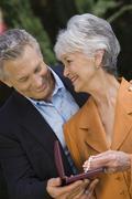 Senior Husband Gifting necklace To Wife - stock photo