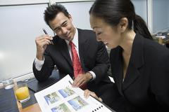 Stock Photo of Businessman Showing Property Samples To His Business Partner