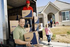 Stock Photo of Unloading Delivery Van In Front Of House