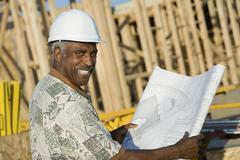 Mature Man In Hardhat With Blueprint At House Construction Site - stock photo
