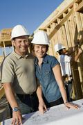 Stock Photo of Couple In Hardhats With Blueprint At House Construction Site
