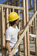 Construction Worker Holding Up Plank - stock photo