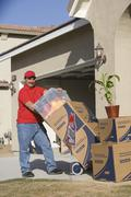 Stock Photo of Man Unloading Boxes In Front Of New House